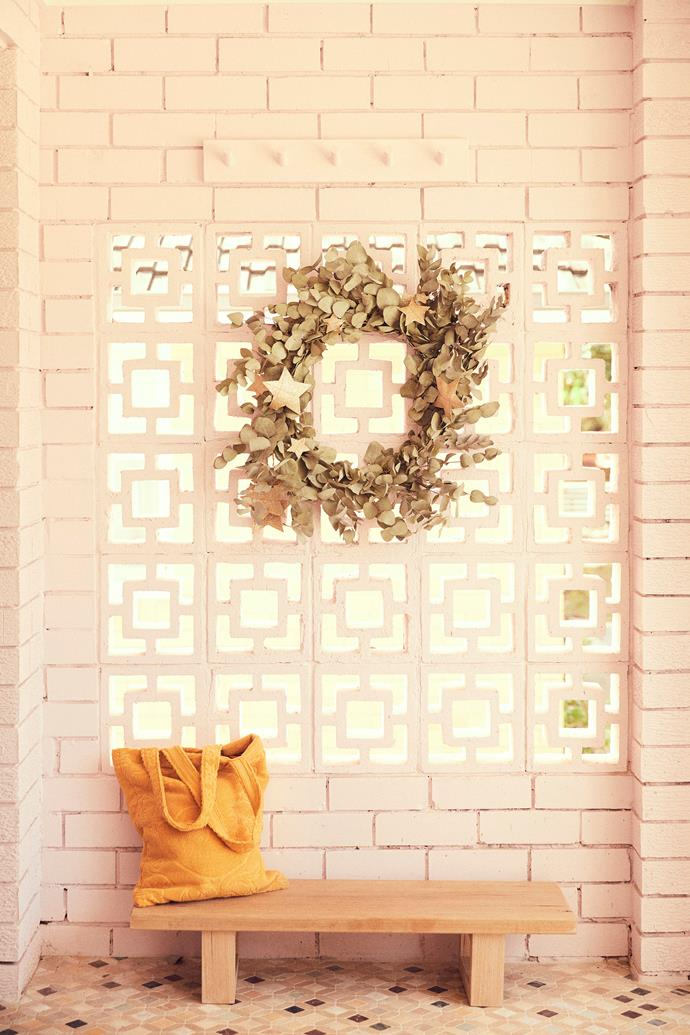 A handmade wreath by Wilderness Flowers hangs at the home's entrance. A Tigmi Trading bag rests on the custom bench.