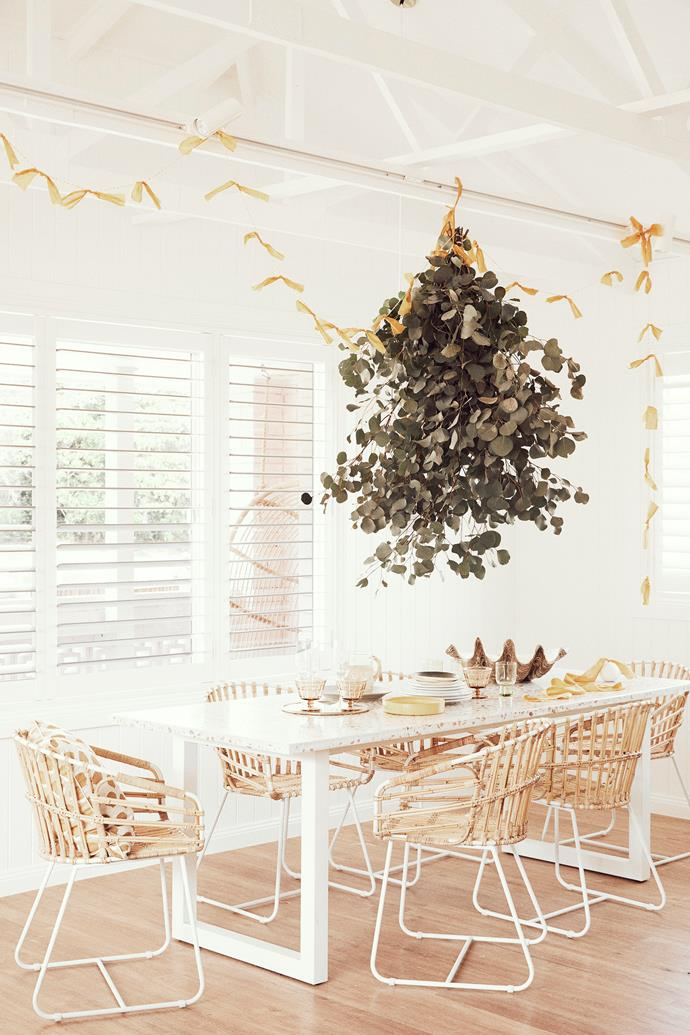 Vorsen chairs sit at the marble dining table, also custom-made. Claire sets it with Nikau plates and glassware and a yellow dish from Markett. A bunch of eucalyptus from Wilderness Flowers and a garland made from strips of cotton hang above.