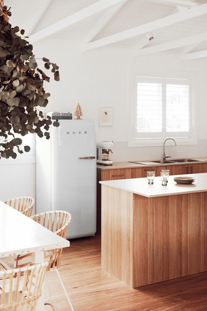 """In the kitchen, a wooden Christmas tree from Spotlight perches on the retro Smeg fridge. """"I usually have a very maximalist style,"""" Claire admits. """"But for our beach house we wanted something super pared-back and uncluttered so there's less to keep tidy."""""""