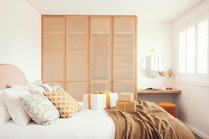In one of the guest bedrooms, a large rattan wardrobe provides ample storage. The bed is made with I Love Linen sheets, while a vanity corner consists of a Fenton&Fenton pouf and Life Interiors mirror.