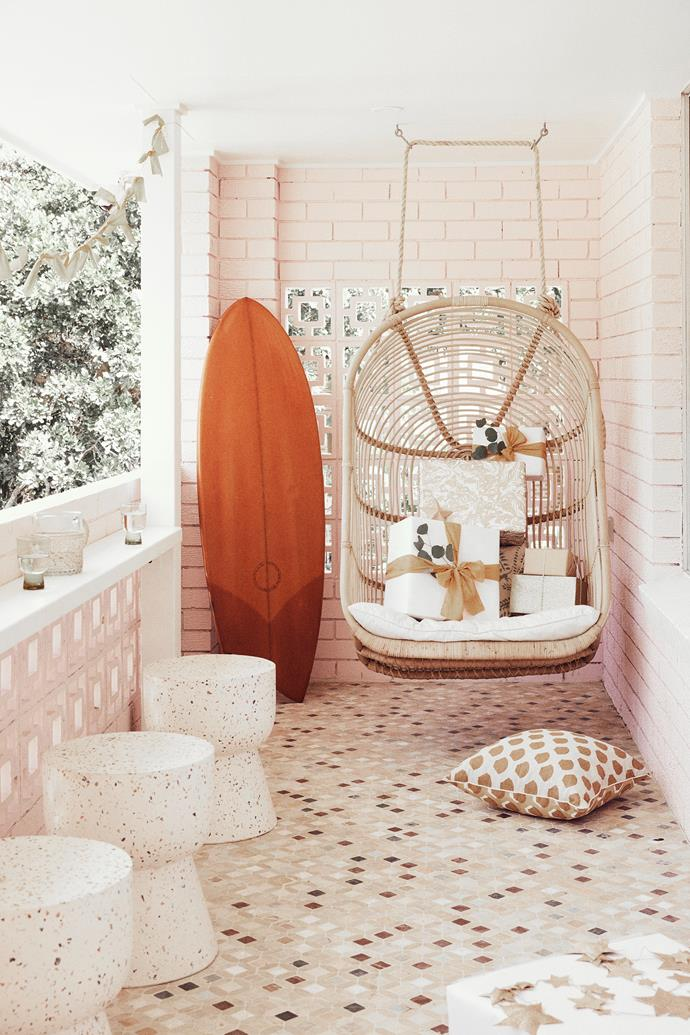 """The balcony is Claire's favourite spot. """"I love the tiles with the terrazzo Fenton&Fenton stools, the hanging chair from Byron Bay Hanging Chairs and most importantly, the people watching."""""""