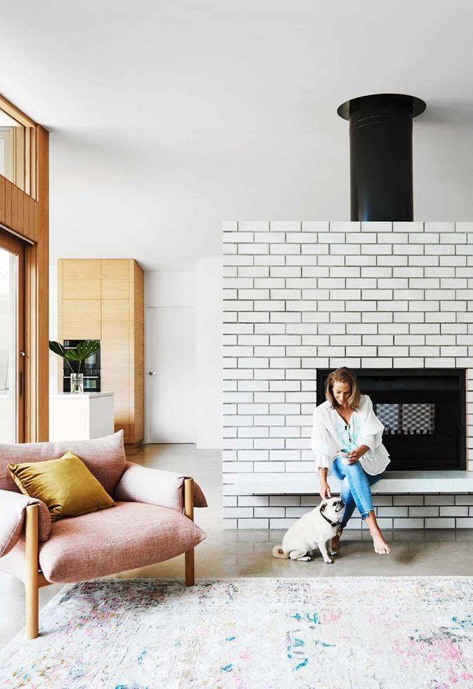 """**Living** The fireplace gives a nod to the mid-century modern style of the original house. """"It really speaks to you when you enter the house,"""" says architect [Steve Tillinger](https://wmkarchitecture.com/