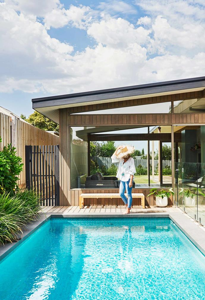 """**Exerior** Georgia has some rare me-time by the pool, which is built along the length of the home and adjacent to the kitchen/dining zone. Behind her is the kids' playroom. As well as the cedar timber with a grey Cutek finish, the house is constructed in Steel bricks from Austral's Industrial range. The wooden bench is from [GlobeWest](https://www.globewest.com.au/