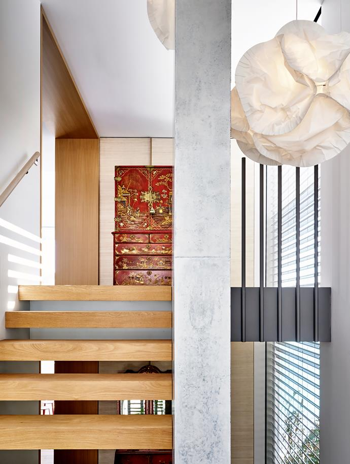 A Frank Gehry 'Cloud' pendant light hangs in the stairwell. American oak treads and off-form concrete blade wall.