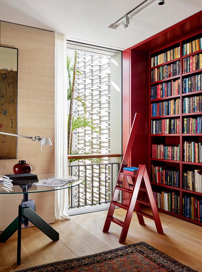Seagrass wallpaper in the library. Custom step ladder. De Padova 'Vidun' table. Artemide 'Tolomeo' lamp. American oak flooring from Precision Flooring.