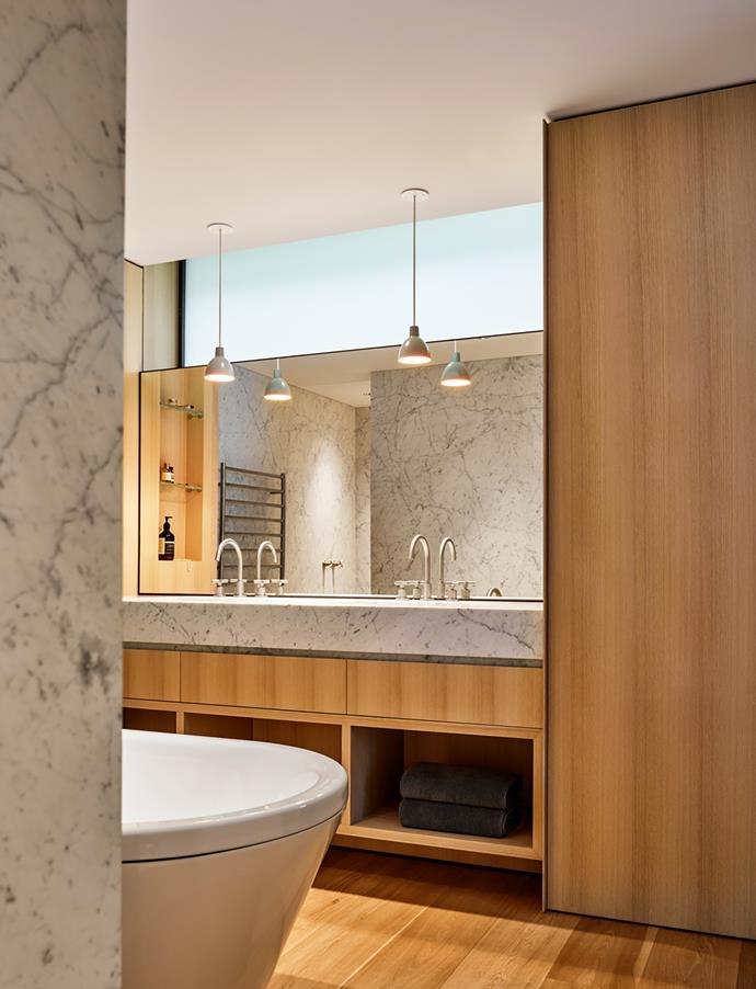 American oak joinery in the bathroom. Astra Walker Icon+ taps. Carrara Gioia marble bench top. Louis Poulsen 'Toldbod 120' duo pendants from Living Edge.