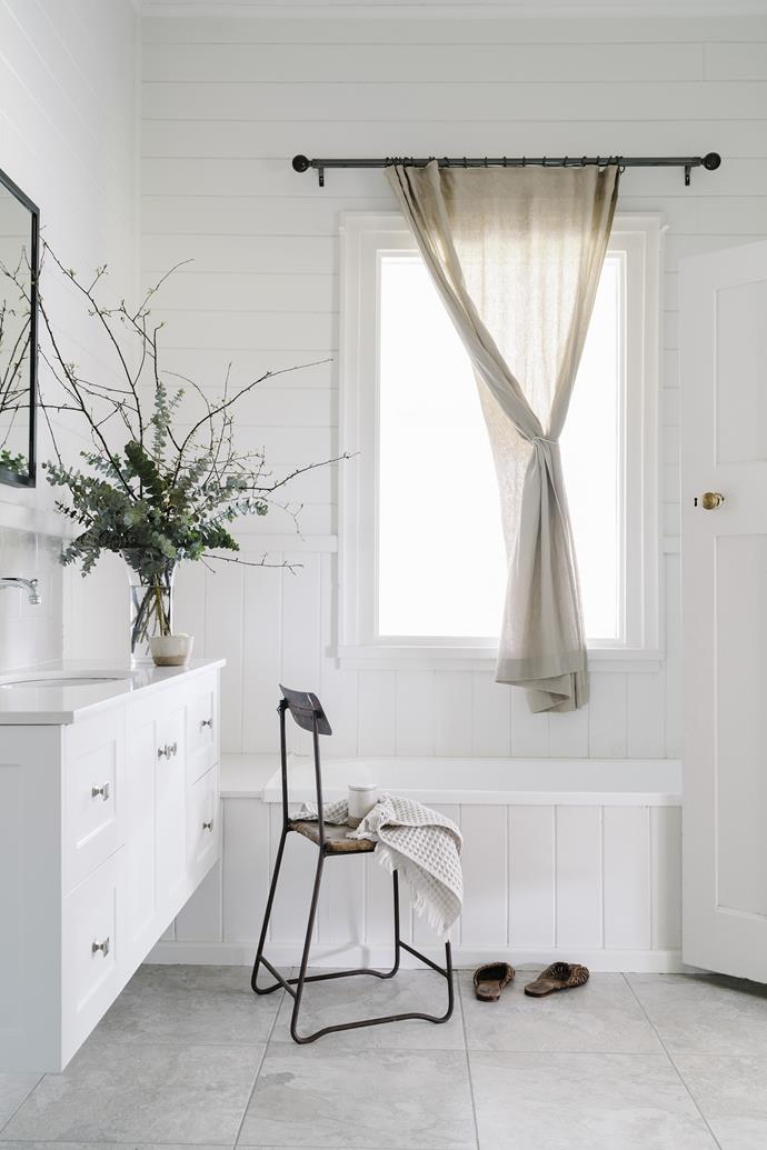 The bathroom features timber panelling to match original details elsewhere in the home.