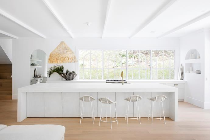 Concrete with a rough finish was used for the benchtops and doors under the island. The cabinets are white-washed timber and brass taco handles were custom made by CJ Anderson.