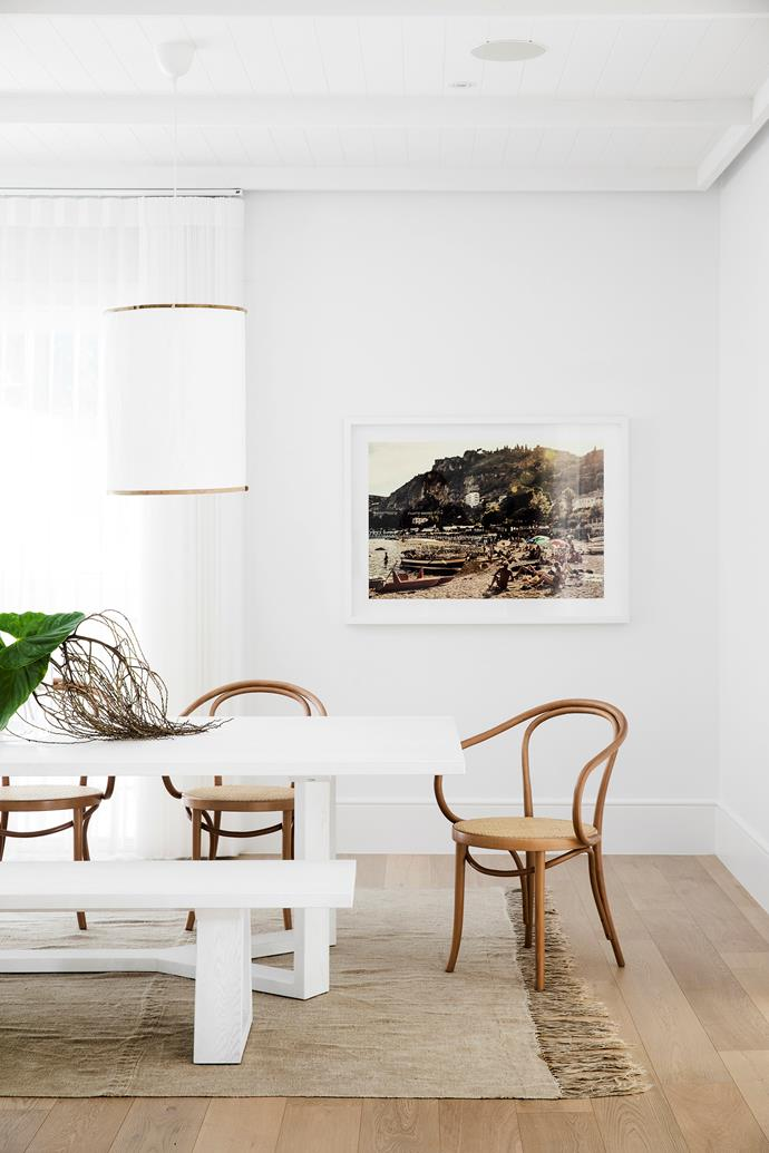A distinct Mediterranean flavour runs through this home, including the dining space. A Cupid dining table and Loop bench seat, both  from The Wood Room, are flanked by classic Le Corbusier chairs, while a Côte Salt linen pendant hangs above. The Beach of Isola Bella, Sicily print by Damian Bennett and rug from House of Orange also fit the brief.