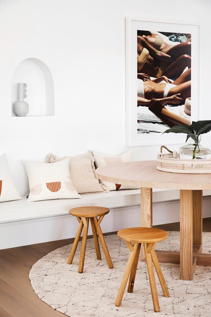 A custom bench seat from Concrete Nation blends seamlessly into the wall around the family's breakfast nook. The soft white-washed timber of the Freedom 'Cove' table complements the engineered timber flooring, chosen for its durability and cost-effectiveness, while Piccolo stools sit on top of the Khofri rug – both also from Freedom.