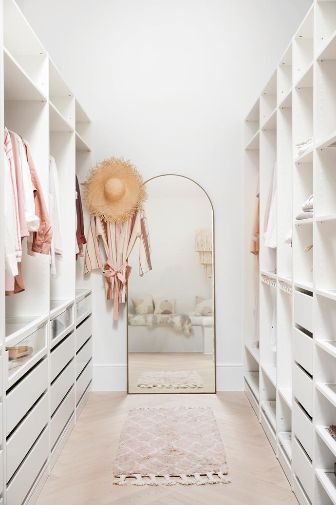 The couple used cost-effective Ikea cabinetry in the walk-in wardrobe, with flooring laid in a herringbone pattern for a luxe touch. The Savannah arched mirror is from Salt X Steele.