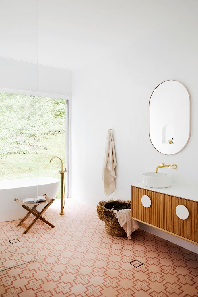 "The main bathroom was inspired by the indoor/outdoor bathrooms of Bali and includes bi-fold doors that open to the large wrap-around balcony surrounded by lush greenery. ""It's fun for the kids,"" says Sophie. ""Our dogs sit and play with them while they're in the bath."
