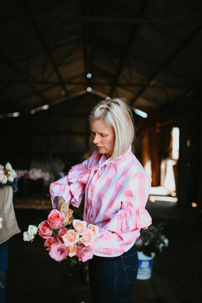Floral stylist Suzie Meers trimming roses in the woolshed, wearing a  Binny blouse from St Louis Boutique in Wellington, NSW.