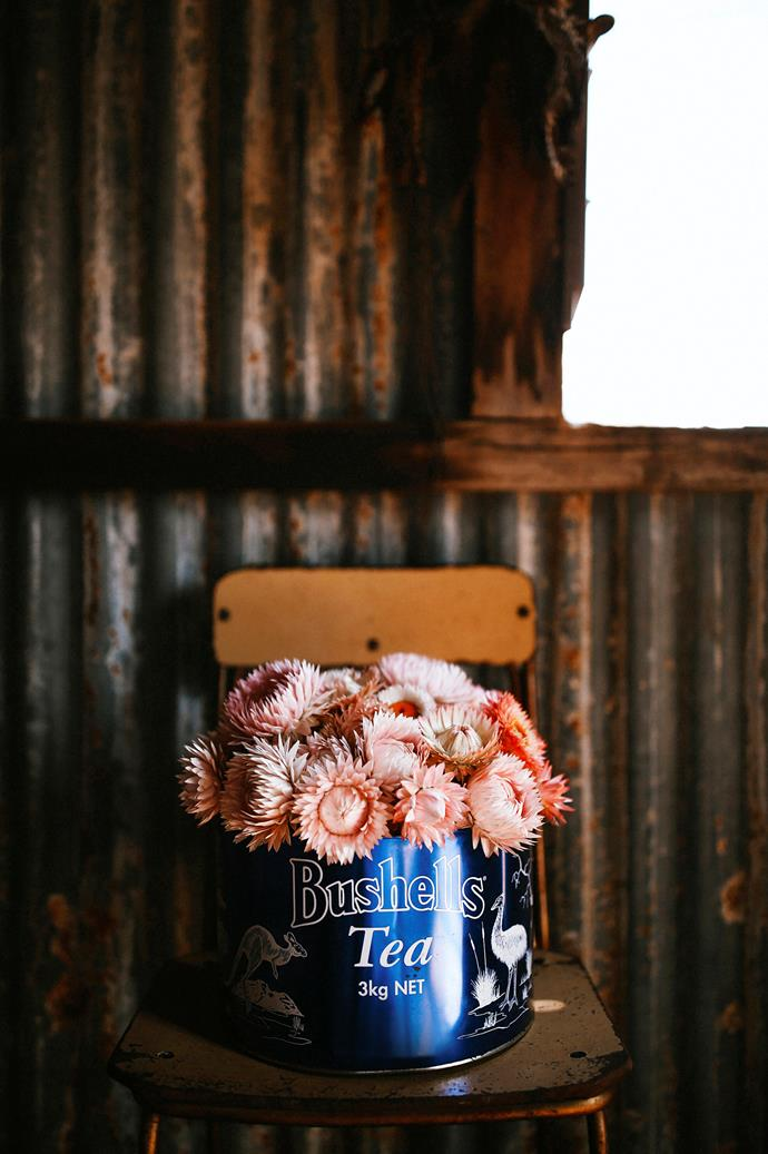 A Bushells loose-leaf tea cannister makes a rustic vase for paper daisies.