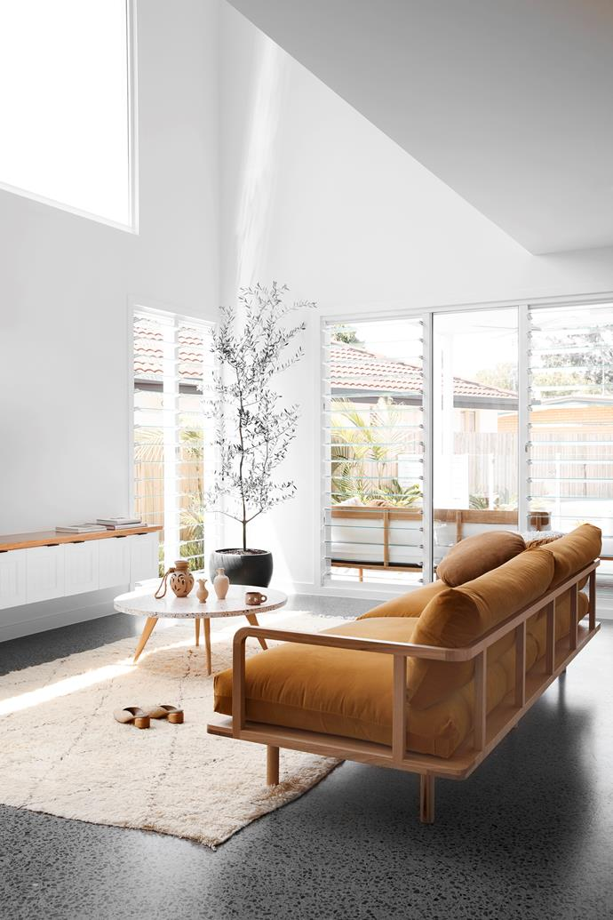 """The couple love to chill on their Pop & Scott sofa in the living area after a long day of work. """"I love the raised Cathedral ceiling – it makes the space feel so grand,"""" Ellie says. The room also features louvre windows and built-in storage, a plush rug from Blush & Ochre and a stately olive tree in its Bunnings pot."""