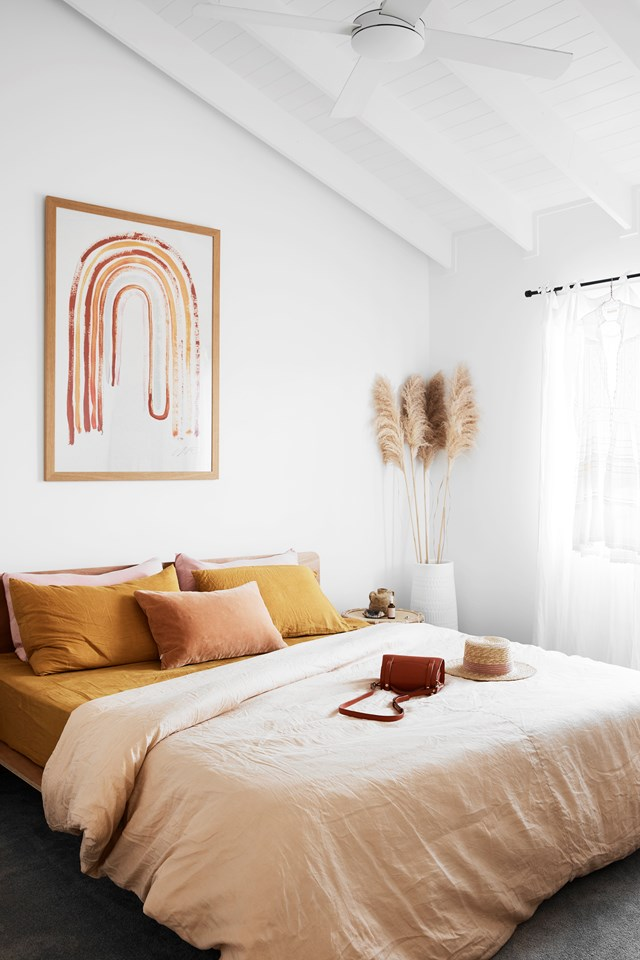 """Earthy tones combined with soft pinks and natural finishes inject this bedroom with warmth and texture. """"The statement rainbow print by Tess Guinery above our bed makes me feel so happy every time I enter,"""" says homeowner Ellie Bullen, who has continued this colour scheme throughout the rest of her gorgeous [Gold Coast home](https://www.homestolove.com.au/ellie-bullen-gold-coast-home-20988