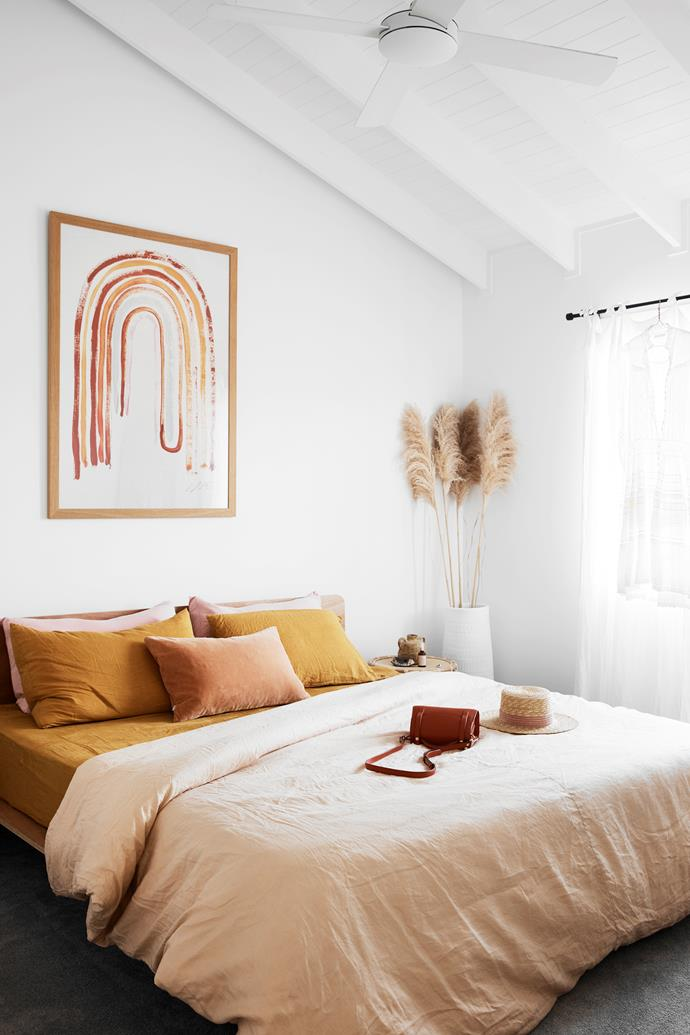 "The couple's bedroom has the added convenience of a walk-in robe and ensuite. Ellie's favourite feature in the room itself? ""The statement rainbow print by Tess Guinery above our bed makes me feel so happy every time I enter."" Their Koala bed is made with sheets from I Love Linen, the side table is by Trader Trove and the vessel holding pampas grass is by The Clay Date."