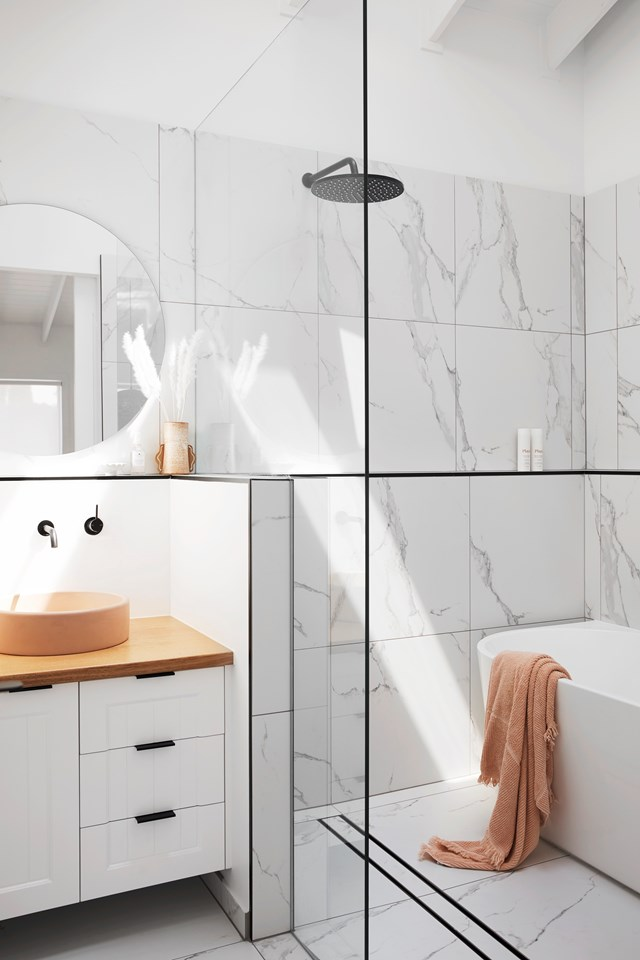 "Marble-look tiles paired with matte black fixtures, give the guest bathroom in [Ellie Bullen's Gold Coast home](https://www.homestolove.com.au/ellie-bullen-gold-coast-home-20988|target=""_blank"") a modern edge. The Tasmanian oak-topped vanity and the peach-coloured Nood Co concrete basin inject colour and warmth."