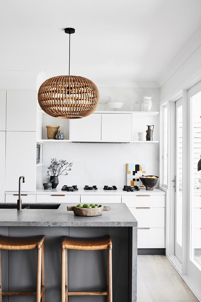 Pitt Cooking burners are set into the Caesarstone Rugged Concrete bench. Leather handles from Made Measure punctuate the cabinetry. Custom pendant light and stools from Indonesia.