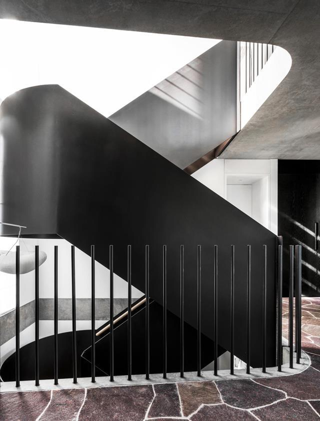 """Architect Nick Tobias of Tobias Partners designed a sinuous gleaming steel staircase that snakes its way up through the [three-storey abode](https://www.homestolove.com.au/ultra-modern-home-with-harbour-views-and-lush-tropical-gardens-20922