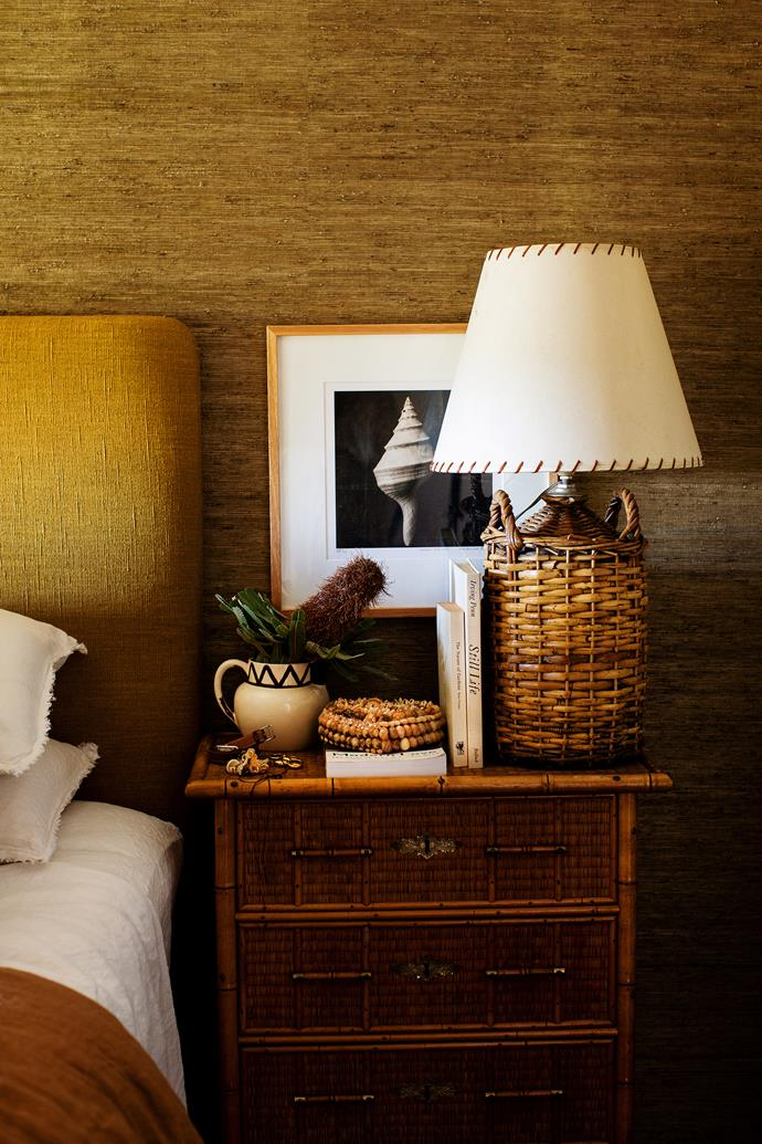 The grasscloth wallpaper blends seamlessly with the custom bedhead.