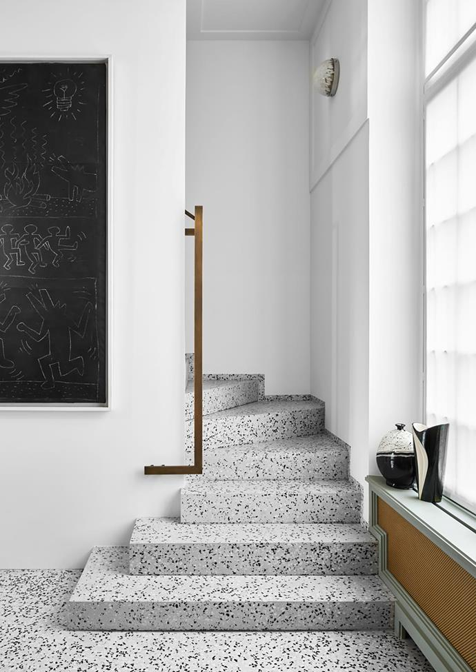 Speckled terrazzo captures the tones of the apartment's white, black and grey palette. Brass railing by Humbert & Poyet. Subway Drawings (1989) artwork by Keith Haring.