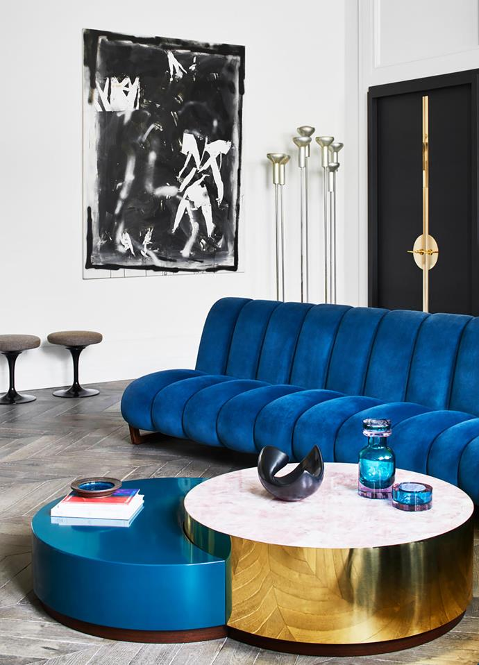 A David Ostrowski artwork hangs above a pair of stools by Eero Saarinen in the living room. Floor lamps by Gino Sarfatti. 'Grand Théodore' sofa and 'Gabrielle' coffee table, both by Humbert & Poyet.