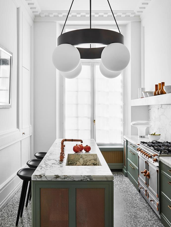 Adding drama to the kitchen is the 'Asterios' suspension light in bronze and frosted glass by Humbert & Poyet which hangs above custom cabinets in a painted finish by Farrow & Ball with brass trim and benchtops in Arabescato marble.