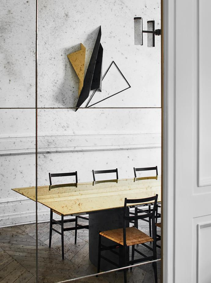 Reflected in a mirrored finish in the formal dining room, Cassina 'Superleggera' chairs by Gio Ponti surround an 'Appolline' table by Humbert & Poyet with a wall sculpture made in timber and metal by Berlin-based artist Katja Strunz.