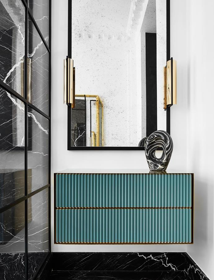 Console in brass and hand-brushed lacquer beneath a mirror and sconces, all by Humbert & Poyet, topped with a sculptural object by Kelly Wearstler.