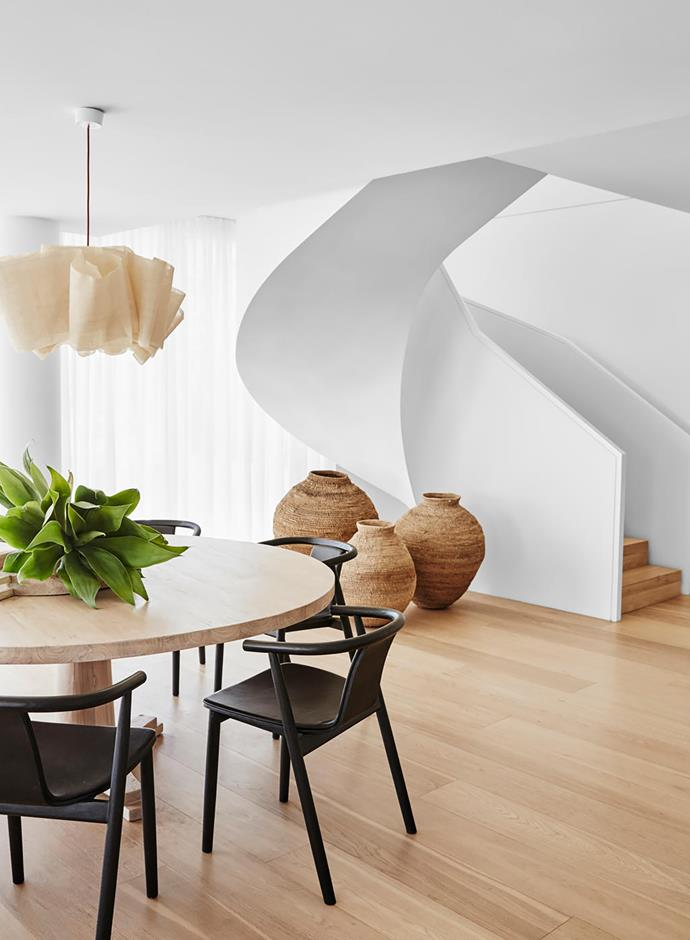 Dining table with black 'Kiki' chairs from MCM House beneath a Pinch 'Anders' pendant light from Spence & Lyda. Baskets from Orient House under the staircase.