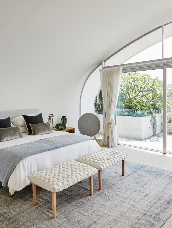 In the master bedroom, Iosis Paris velvet cushions from Francalia sit on a 'Nook' bed from Jardan with a pair of Ligne Roset 'Ruché' ottomans from Domo. On the bedside table, L'Objet 'Cenote' vase from Becker Minty and 'Lumi' table lamp from Articolo. 'Beoplay A9' speaker from Bang & Olufsen. Antique Turkish rug from Behruz.