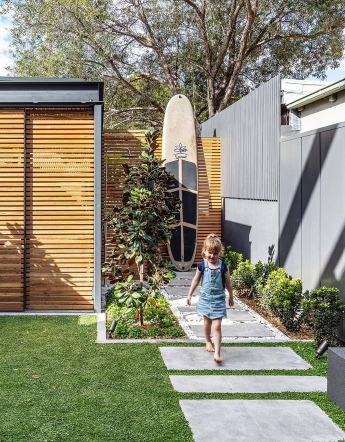 The builder's young daughter Danielle strides across the concrete steppers. The carport has blackbutt doors and can be used as an extra entertaining space. Landscape design by Podology.