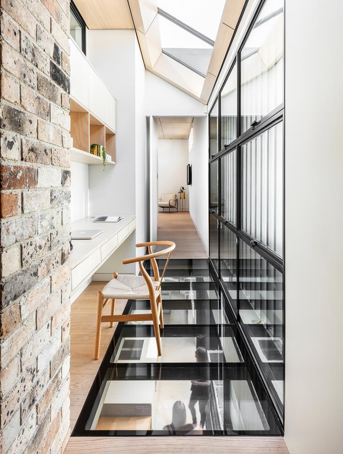 Bricks from the adjoining semi's chimney were repurposed in the upstairs hall of this home. Windows by Steel Windows Australia, skylight by Atlite Skylights and joinery by Nu Space.