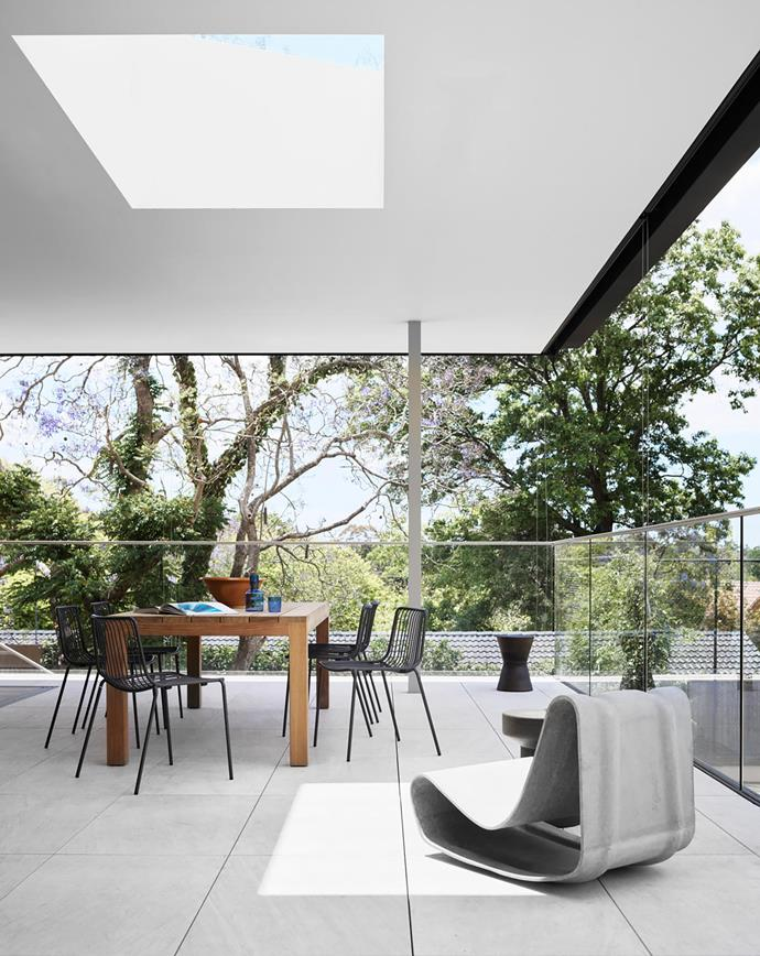 The dining table is positioned under a giant skylight, ensuring this outdoor space – just off the family room – is bathed in light, even in winter. Pedrali 'Nolita' dining chairs, Chunky dining table, Willy Guhl 'Loop' chair and Chess stool, all Robert Plumb.