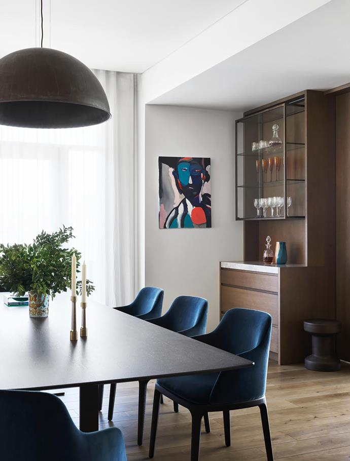 Eileen dining table, B&B Italia. Grace dining chairs from Poliform, upholstered in Danubio 58 velvet. Il Fanale pendant light, LightCo. Curtains in Studio Collection 'Sinua' fabric, Tigger Hall Design. Artwork by Nunzio Miano, Curatorial+Co. Drinks cabinet designed by Jorge Hrdina.