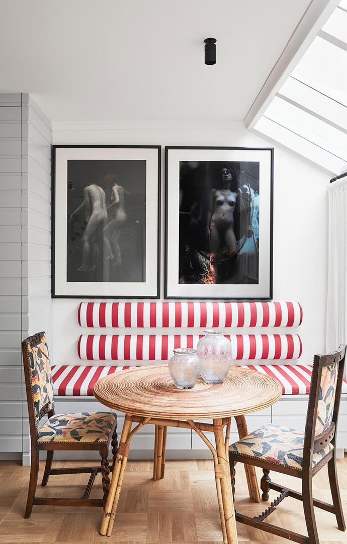 A custom-designed bench upholstered in Ralph Lauren Home­ fabric anchors a pair of Bill Henson artworks in this cafe-style setting. The 1930s cane table, 1920s Italian chairs and Daum vases are naturally illuminated by skylights above.