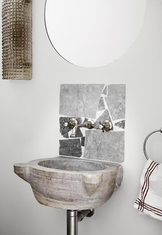 The same tiles adorn a larger basin with brushed aluminium joinery and a 1950s French sconce.