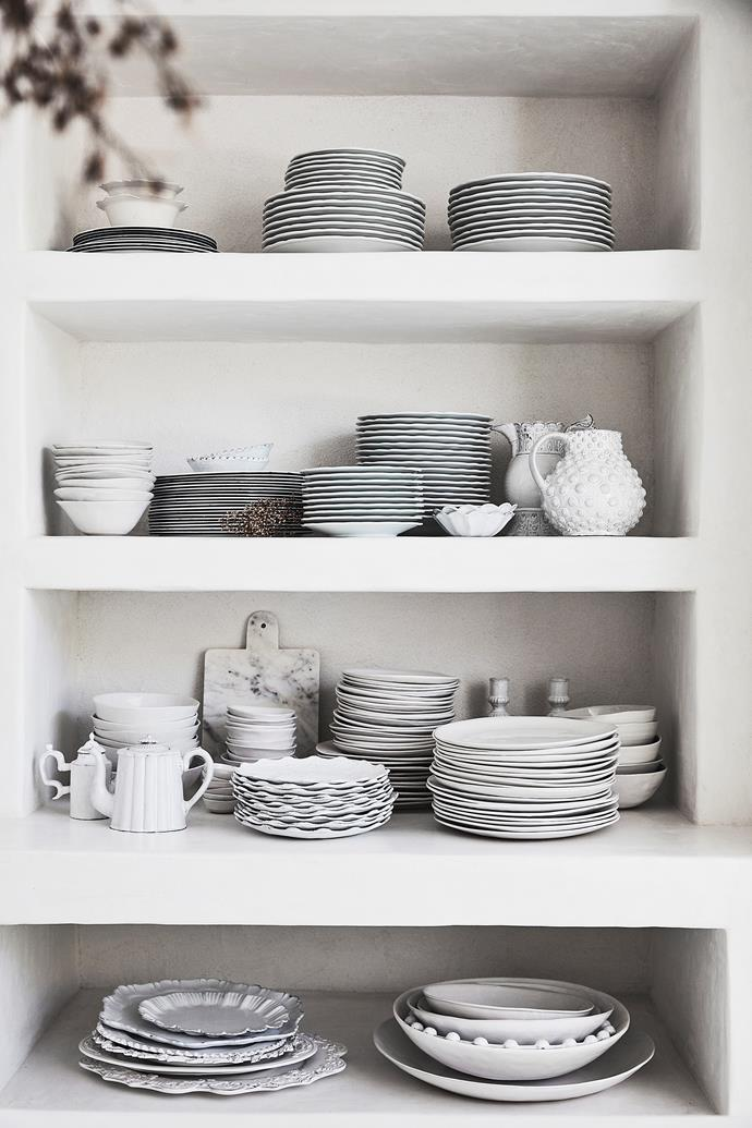 Plates and bowls by French brand Astier de Villatte are piled high on open shelves to create decorative interest – and provide easy access.