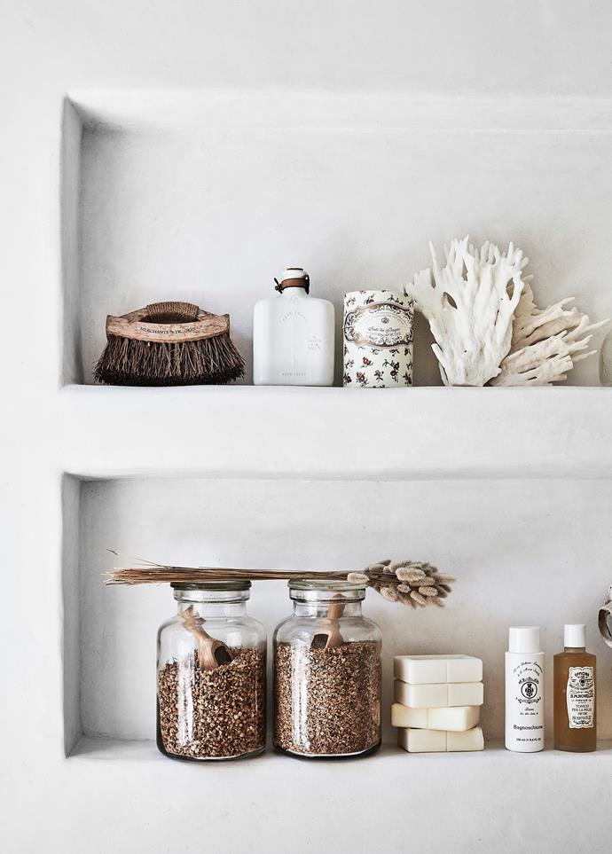 Even the shelves and bath caddy are decorated with white-palette-friendly accessories, including jars of bath tea and toiletries from centuries-old apothecary brand Santa Maria Novella.