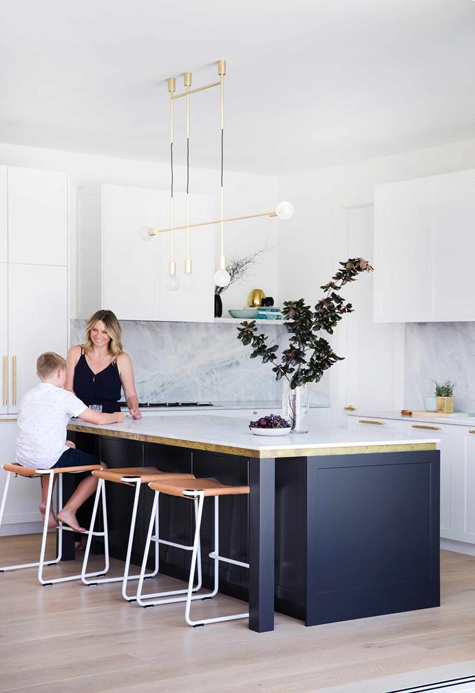 **Kitchen** Deb and Harry at the island bench featuring bespoke brass edging. Natural stone reigns supreme here, with luxe Elba marble on the splashback and benchtops.