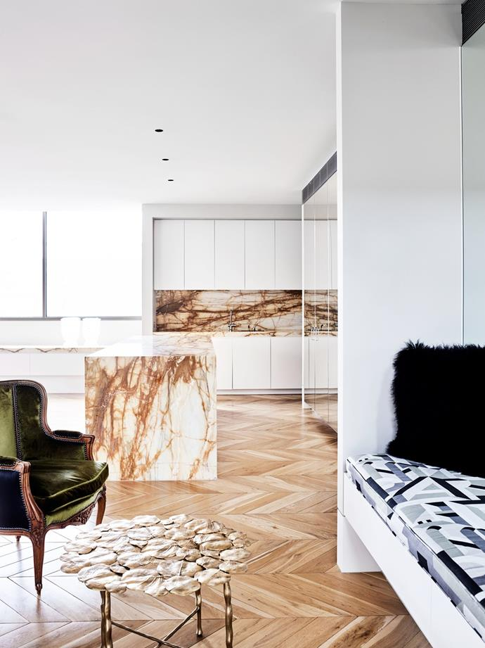 A striking marble island and splashback contrasts with this all-white kitchen while tying in with the parquetry flooring. When working with marble, look for irregular stone styles that won't date and don't be afraid to go bold. *Photo: Mark Roper / Bauersyndication.com.au*