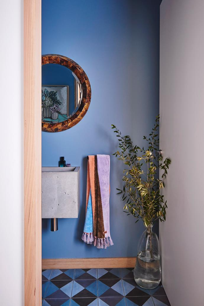 A deep blue paint colour that is also carried through in the floor tiles, gives this small powder room plenty of personality.