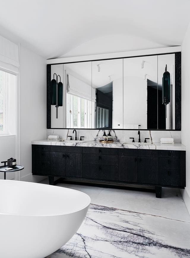 "The main ensuite in this [harbourside](https://www.homestolove.com.au/waterfront-house-nature-inspired-interiors-20420|target=""_blank"") home features opulent slabs of New York marble and a monochrome palette, both of which create a timeless appeal. The mini curve in the ceiling echoes the curve in the roofline of the house."