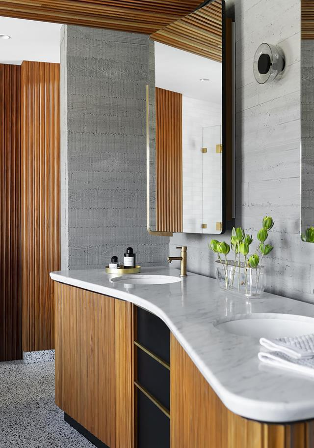 """""""We wanted a feeling of 'wabi-sabi' through the house using robust materials. It's about being a little imperfect and ageing well,"""" says architect Neil Cownie. The ensuite echoes the home's curvilinear form and features the same concrete and ribbed timber seen throughout the abode."""