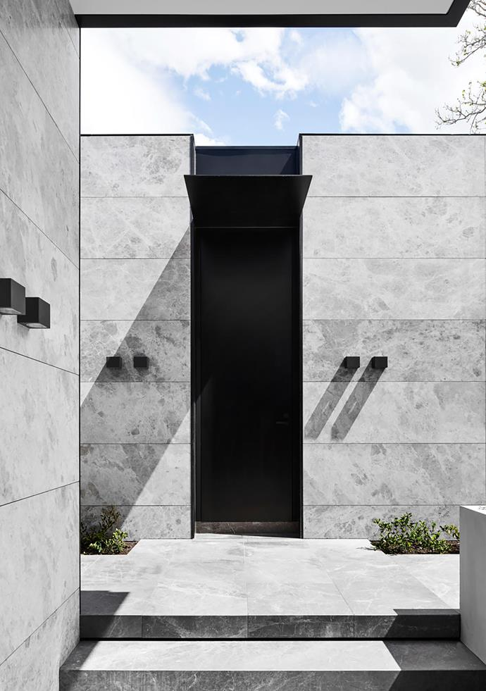 The monolithic entryway makes an impressive welcoming statement. 'Tiga' sconces by Inlite.