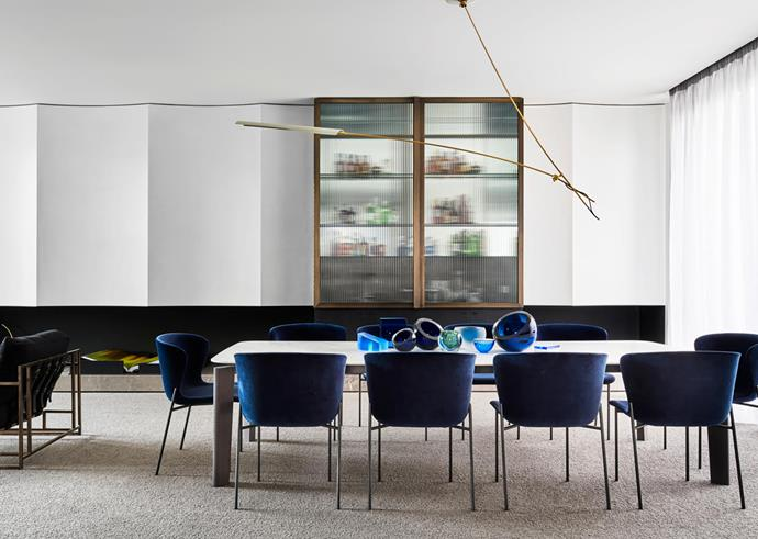 Under the 'Otto' one-arm pendant light by David Weeks from Criteria, the formal dining room features a B&B Italia 'Oskar' table by Vincent Van Duysen from Space with 'La Pipe' chairs by Friends & Founders from Fred International. The table holds a mix of glass objects by Anna Torfs from Space, Tom Dixon from De De Ce, and Philip Low from Hub.