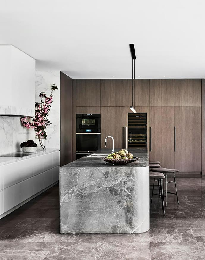 The pendant light in the kitchen was conceived by Mim Design and sourced through Ambience. Living Divani 'Hinge' stools from Space are pulled up at the curved island bench, which is made from two solid slabs of stone.