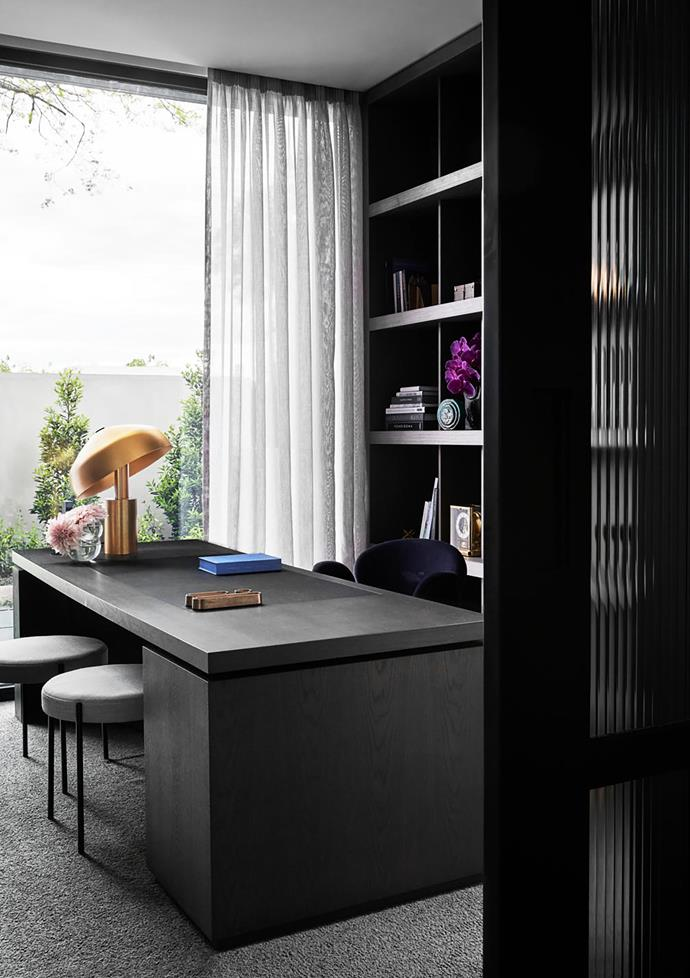 The downstairs study overlooks the garden. A pair of Verpan 'Series 430' stools from Space sit under the custom desk with leather inlay from Zuster. 'Ora' desk lamp by Ross Gardam.