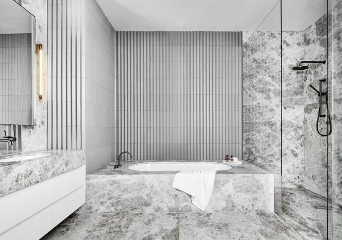 In the master bathroom, proportion was a key consideration. The natural stone is overscaled but balanced by a wall of smaller, pleated tiles. 'Shy' sconce by Bec Brittain from Criteria.